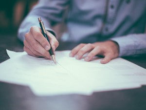 Hand with ball pen signing a document